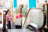 Zwei glückliche junge frauen in einkaufszentrum — Stockfoto