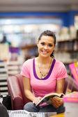 Jeune femme lisant un livre en librairie — Photo