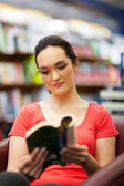 Young woman reading a book in library — Stock fotografie