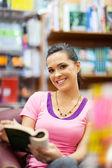 Jeune femme lisant un livre dans la bibliothèque — Photo