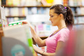Young woman choosing a book in bookstore or library — Stock Photo