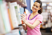 Young woman choosing a book in bookstore — Stock Photo