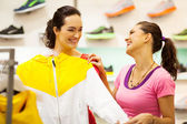 Two young women shopping for sportswear in mall — Stock Photo