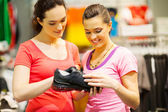 Shop assistant helping customer choosing sports shoes — Stock Photo