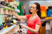 Young female sportswear shop assistant working in store — Stok fotoğraf