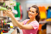 Happy young woman shopping for sports footwear — Stock Photo