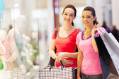 Two happy friends shopping in mall — Stok fotoğraf