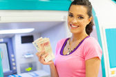 Happy young woman withdrawing or depositing cash at an ATM — Stock Photo