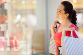 Happy young woman window shopping — Foto Stock
