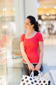 Young woman with shopping bags looking at store showcase — Stock Photo