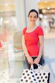 šťastná žena s nákupní tašky v obchoďáku — Stock fotografie