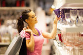 Young woman shopping for glass — Stock Photo
