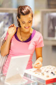 Young woman choosing jewellery in shop — Stock Photo