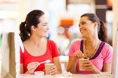 Twee gelukkige vrienden met dranken in café — Stockfoto