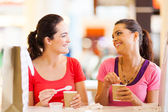 Two happy friends having drinks in cafe — Stock Photo