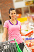 Happy young woman shopping for frozen food in supermarket — Stock fotografie