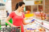 Genç kadın bakkal süpermarket alışveriş yapıyor — Stok fotoğraf