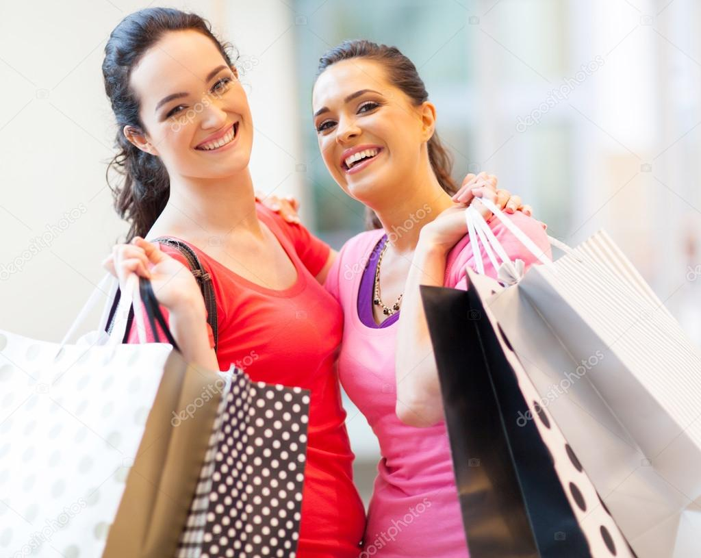 Happy girls with shopping bags in mall — Stock Photo #14904331
