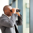 Determined african american businessman using binoculars in office — Stock Photo #14964147
