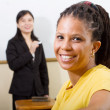 Adult african student in classroom, background is a teacher standing in front of white board — Stock Photo