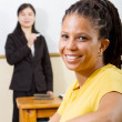 Adult student in classroom, background is teacher standing by white board — Stock Photo