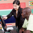 Female chinese teacher teaching computer to african student — Stock Photo