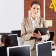 Pretty female high school teacher portrait in computer room — Stockfoto