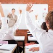 Group of students arms up in classroom — Stok fotoğraf