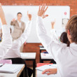 Group of students arms up in classroom — Stockfoto