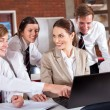 High school teacher and students with laptop in classroom — Foto de Stock