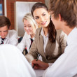 High school teacher interacting with students in classroom — ストック写真