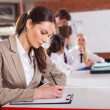 Beautiful school teacher preparing lesson in classroom - Stock Photo