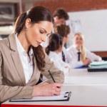 Beautiful school teacher preparing lesson in classroom — Stock Photo