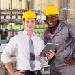 Modern factory manager and worker with tablet computer — Stock Photo