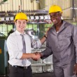Stock Photo: Boss handshaking and praising hardworking worker in factory