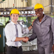 Boss handshaking and praising hardworking worker in factory — Stock Photo