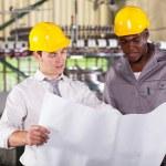 Директор завода и работника, глядя на производственный план — Стоковое фото