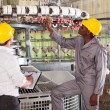 Stockfoto: Textile factory manager and worker checking yarn on weaving machine
