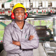 Happy african american textile worker portrait in front of machinery — Stock Photo