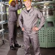 Textile factory worker full length portrait in front of machine — ストック写真