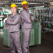 Two industrial workers full length portrait in factory — 图库照片