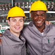:two friendly industrial workers colleagues in factory — Stock Photo