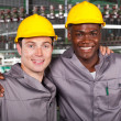 :two friendly industrial workers colleagues in factory — Stok fotoğraf