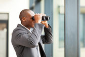 Determined african american businessman using binoculars in office — Stock Photo