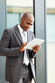 Thoughtful african american businessman with tablet computer in office — Stock Photo