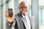 Uomo d'affari americano africano tenendo uno smart phone verso la fotocamera — Foto Stock