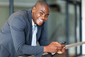 Handsome african american business executive with smart phone — Stock Photo