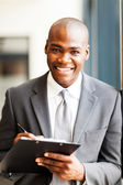 Smiling african american office worker writing report in office — Stock Photo