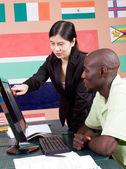 Kvinnlig kinesiska lärare lära datorn till afrikanska student — Stockfoto
