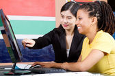 Chinese teacher teaching african student in classroom — Stock Photo